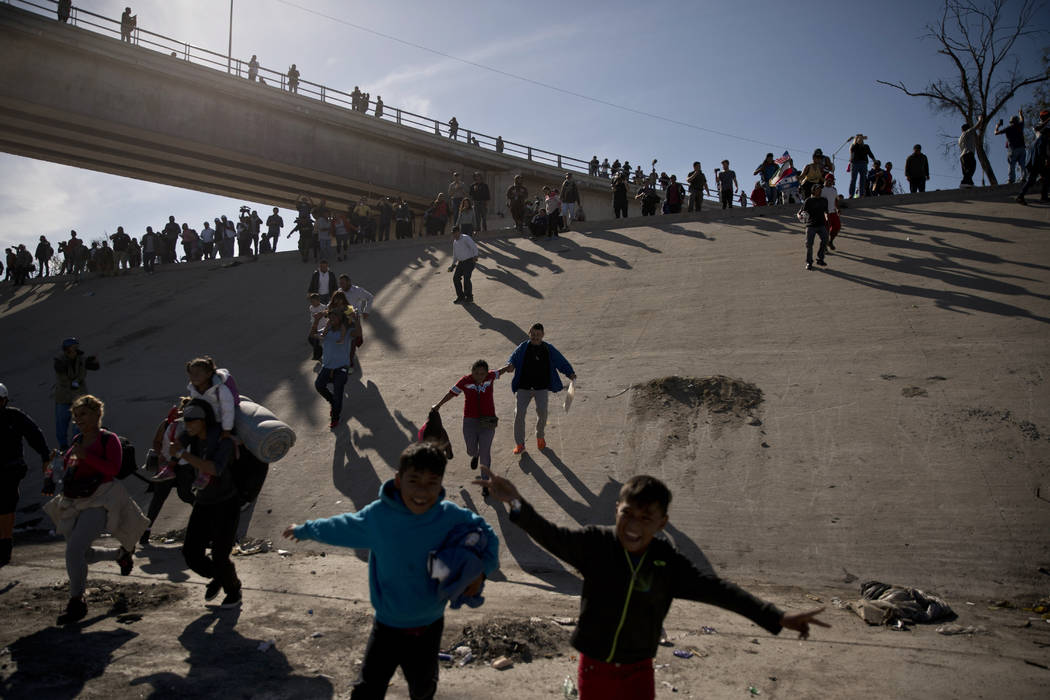 Migrants cross the river at the Mexico-U.S. border after pushing past a line of Mexican police at the Chaparral crossing in Tijuana, Mexico, Sunday, Nov. 25, 2018, as they try to reach the U.S. ( ...