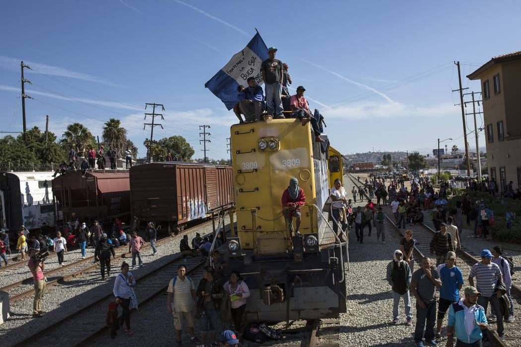 A migrant waves an Honduran flag along the railroad tracks at the Mexico-U.S. border in Tijuana, Mexico, Sunday, Nov. 25, 2018, as a group of migrants tries to reach the U.S. (Rodrigo Abd/AP)