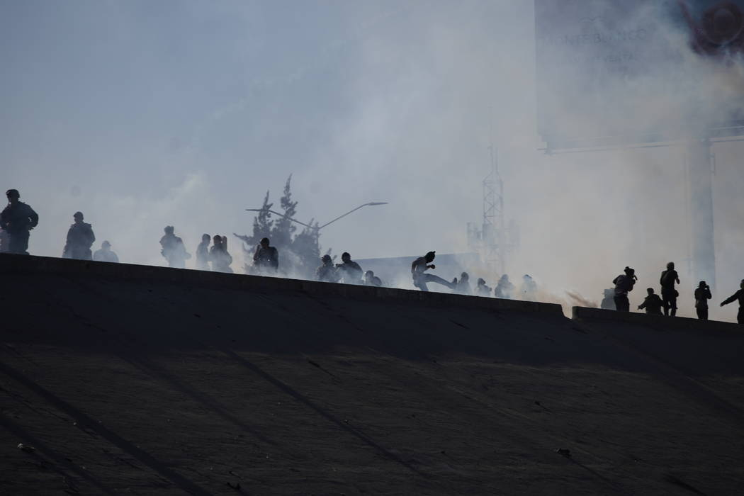 Migrants run from tear gas launched by U.S. agents, amid members of the press, at the top of a riverbank at the Mexico-U.S. border after a group of migrants pushed past Mexican police at the Chapa ...