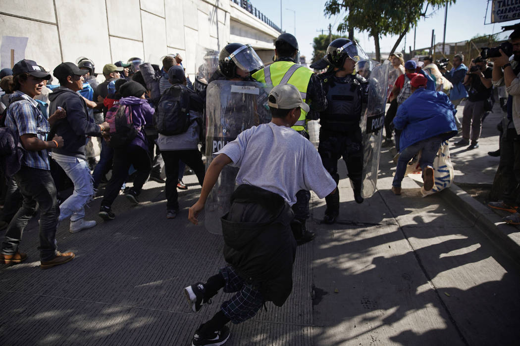 Migrants break past a line of police as they run toward the Chaparral border crossing in Tijuana, Mexico, Sunday, Nov. 25, 2018, near the San Ysidro entry point into the U.S. More than 5,000 migra ...