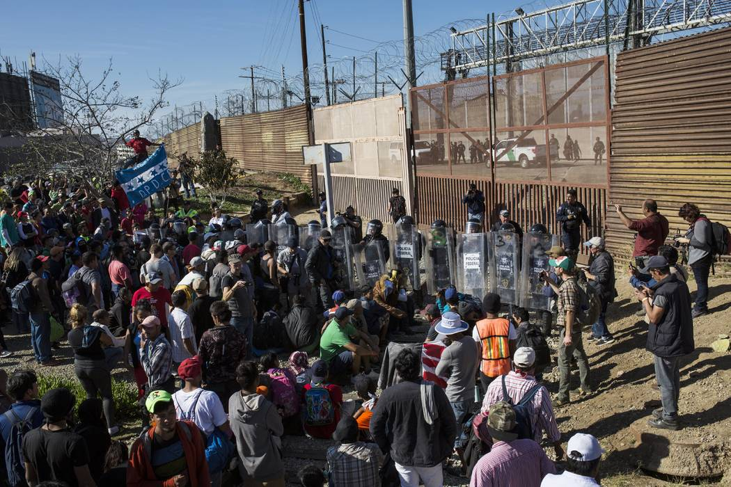 Migrants stand at the Mexico-U.S. border wall where Mexican federal police stand guard at the Chaparral crossing in Tijuana, Mexico, Sunday, Nov. 25, 2018, as they try to reach the U.S. (Rodrigo A ...