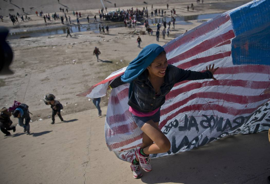 A migrant woman helps carry a handmade U.S. flag up the riverbank at the Mexico-U.S. border after getting past Mexican police at the Chaparral border crossing in Tijuana, Mexico, Sunday, Nov. 25, ...