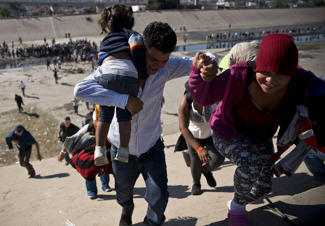 Migrants walk up a riverbank at the Mexico-U.S. border after getting past a line of Mexican police at the Chaparral border crossing in Tijuana, Mexico, Sunday, Nov. 25, 2018, as they try to reach ...