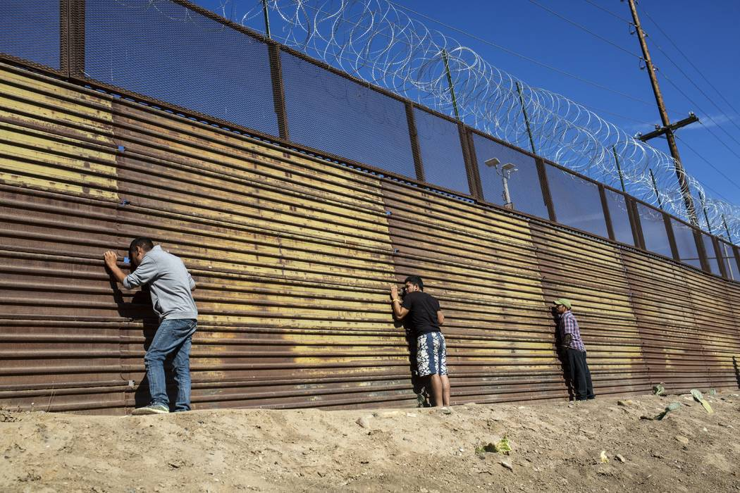 Migrants peer through the border wall after pushing past Mexican police at the Chaparral crossing in Tijuana, Mexico, Sunday, Nov. 25, 2018, as they try to reach the U.S. (Rodrigo Abd/AP)