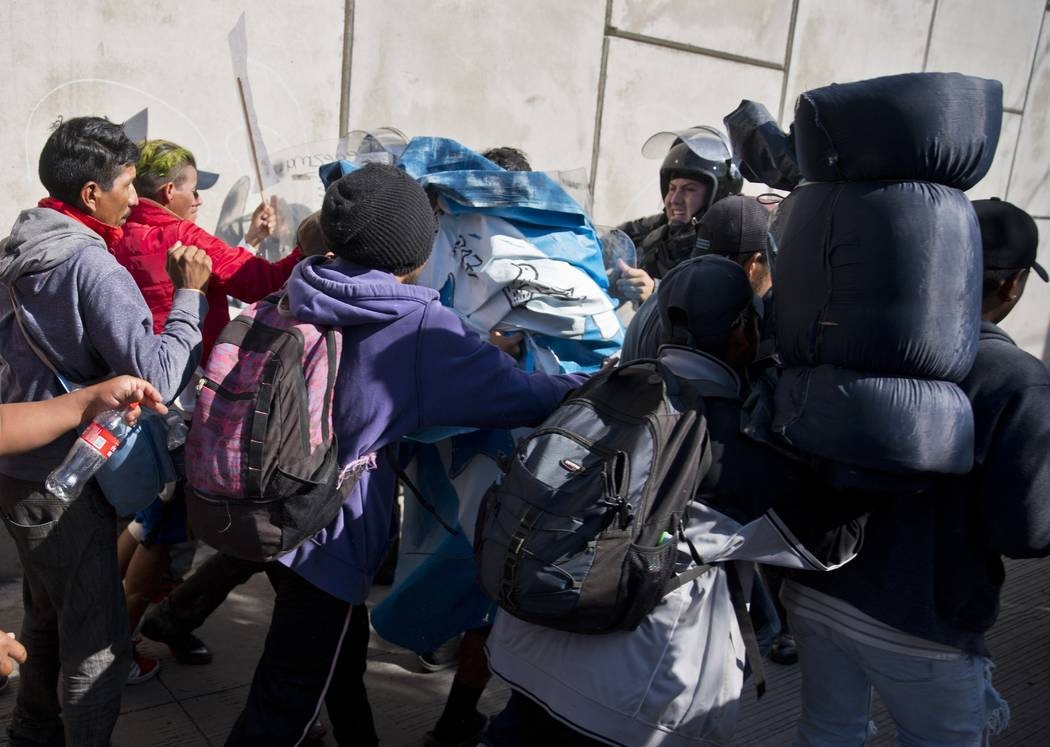 Migrants push past Mexican police at the Chaparral border crossing in Tijuana, Mexico, Sunday, Nov. 25, 2018, as they try to reach the United States. The mayor of Tijuana has declared a humanitari ...