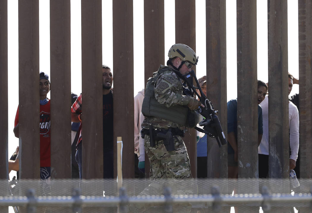 U.S. Customs and Border Protection officers walks along a wall at the border between Mexico and the United States, as seen from San Diego on Sunday, Nov. 25, 2018. Migrants approaching the U.S. bo ...