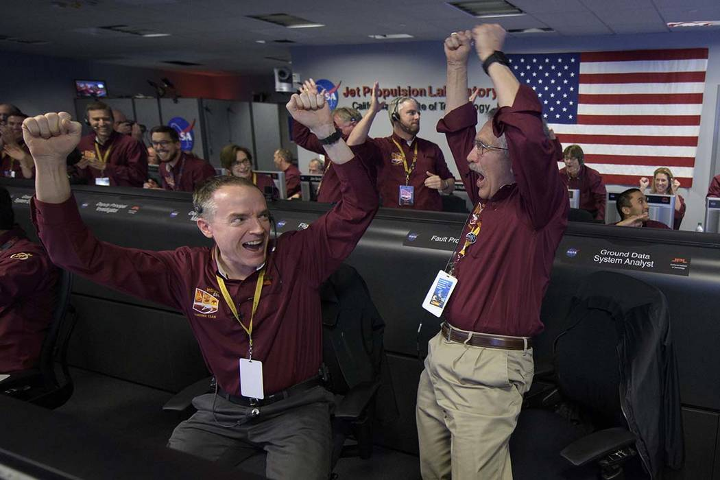In this image provided by NASA, Mars InSight team members Kris Bruvold, left, and Sandy Krasner rejoice, Monday, Nov. 26, 2018, inside the Mission Support Area at NASA's Jet Propulsion Laboratory ...
