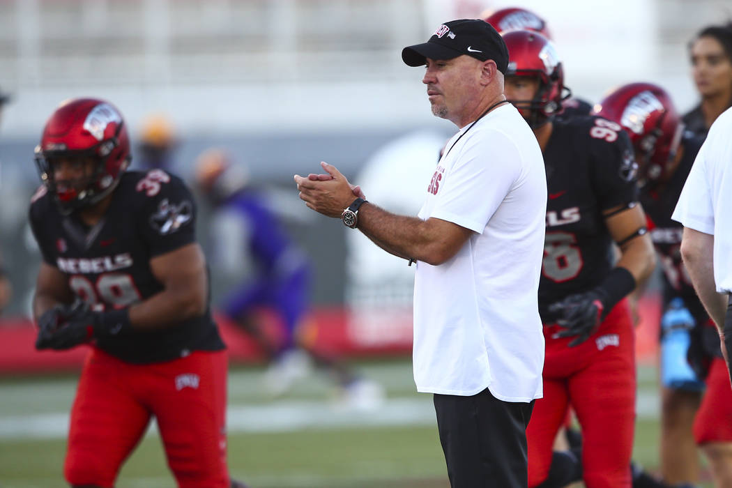 UNLV Rebels head coach Tony Sanchez watches as his players warm up before the start of a football game against Prairie View A&M Panthers at Sam Boyd Stadium in Las Vegas on Saturday, Sept. 15, 20 ...