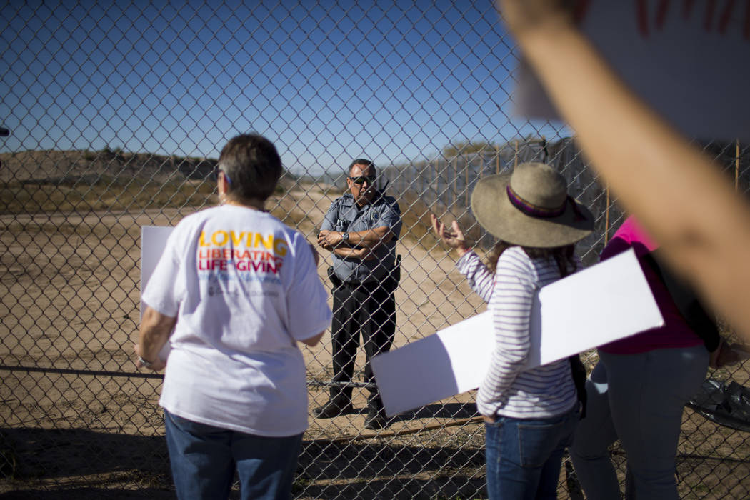Protesters talk to a guard inside the Tornillo detention camp holding more than 2,300 migrant teens in Tornillo, Texas, Nov. 15, 2018. Less than six months after opening, the facility has expanded ...