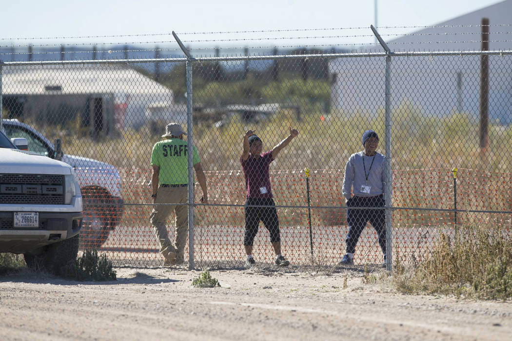 Migrant teens held inside the Tornillo detention camp smile at protestors waving at them outside the fences surrounding the facility in Tornillo, Texas, Nov. 15, 2018. Less than six months after o ...