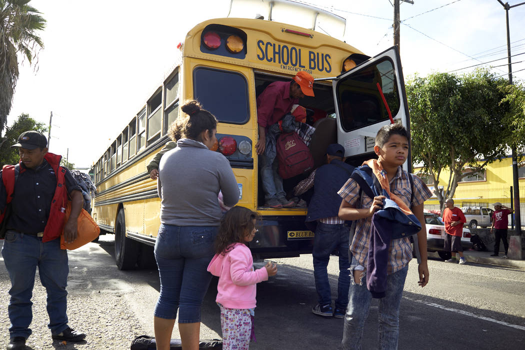 Central American migrants arrive by school bus to a shelter offering breakfast in Tijuana, Mexico, Thursday, Nov. 15, 2018. Members of a migrant caravan started to meet some local resistance as th ...