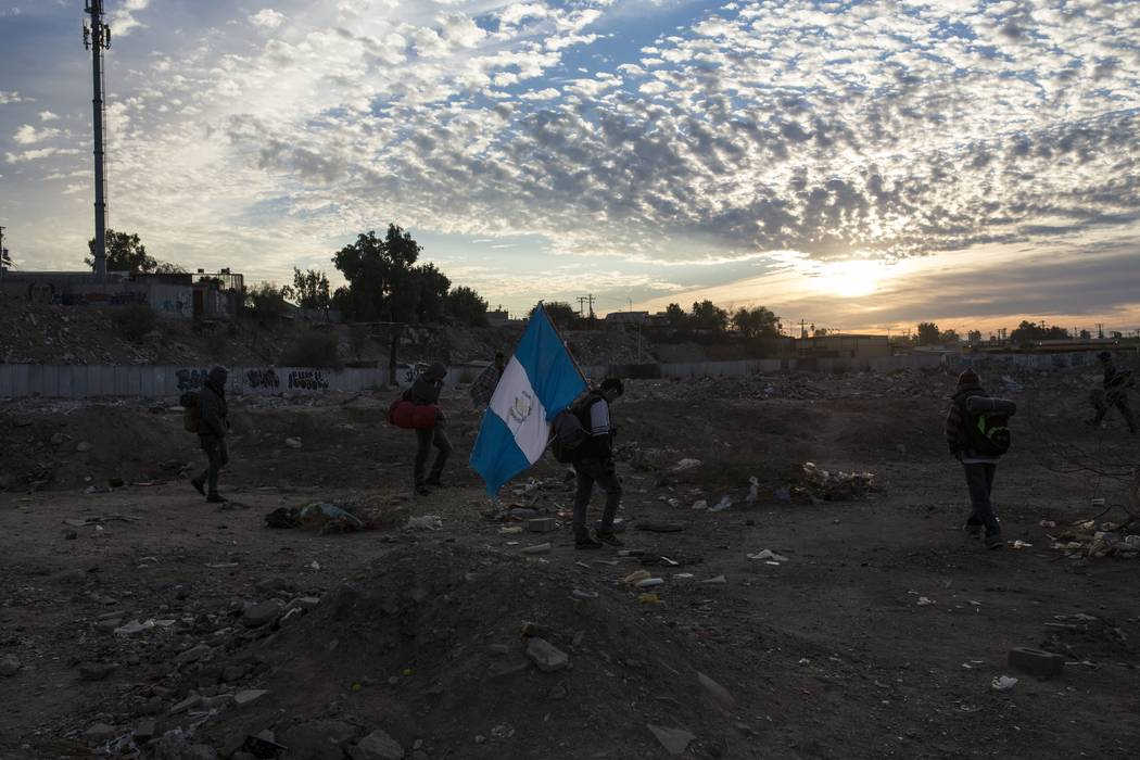 A man traveling with a Central American migrant caravan carries a Guatemalan flag at sunrise as the group leaves Mexicali for Tijuana, Mexico, Tuesday, Nov. 20, 2018. Tensions have built as nearly ...