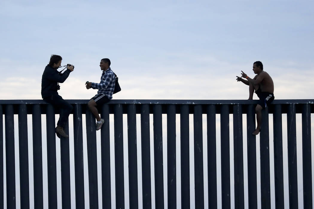 Two Honduran men pose as a photographer, at left, takes their picture after the group climbed the border wall separating Tijuana, Mexico, and San Diego, before climbing back down on the Mexican si ...