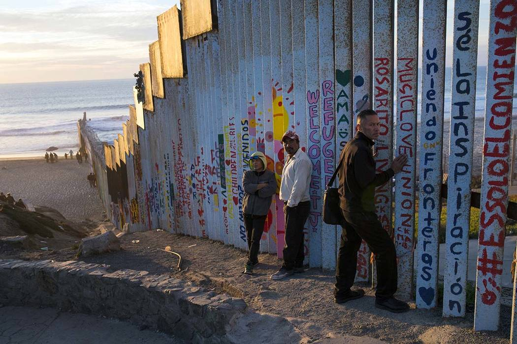 People hang out at the Mexican side of the border structure that separates Mexico from the U.S., at the Pacific Ocean, Tijuana, Mexico, Friday, Nov. 16, 2018. As thousands of migrants in a caravan ...