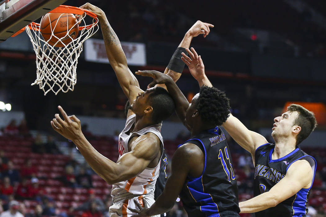 UNLV Rebels forward Shakur Juiston (10) dunks the ball in front of UC Riverside Highlanders guard Eric Rwahwire (13) during the first half of a basketball game at the Thomas & Mack Center in L ...