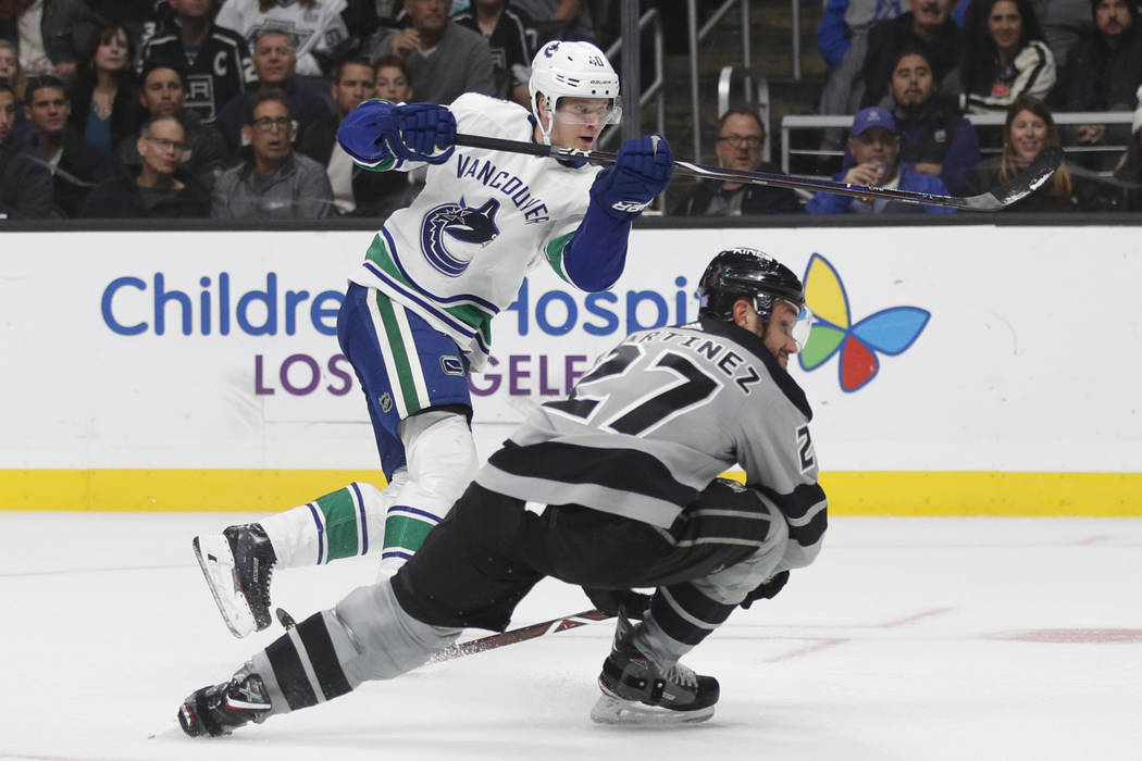 Vancouver Canucks' Elias Pettersson, top, of Sweden, and Los Angeles Kings' Alec Martinez watch the puck hit by Pettersson enter the net for a goal during the third period of an NHL hockey game Sa ...