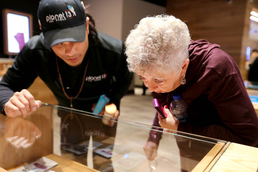 Barbara Strecker of Las Vegas checks out product with the help of budtender Brandon Hang at Planet 13, which bills itself as one of the largest dispensaries in the world, Thursday, Nov. 1, 2018. T ...