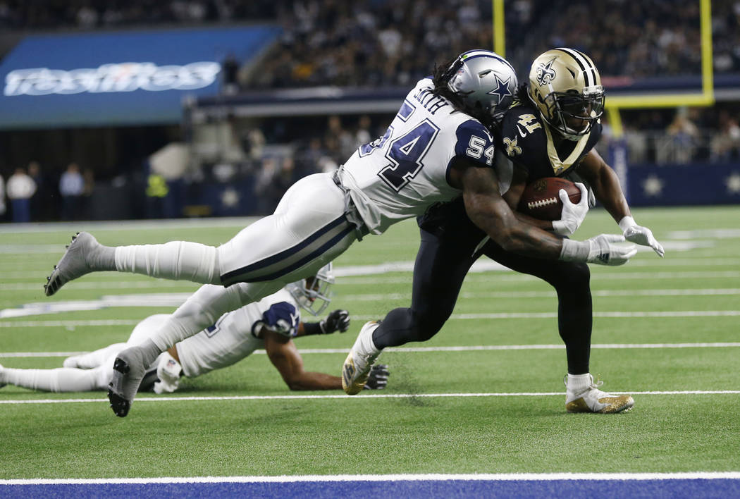 New Orleans Saints running back Alvin Kamara (41) is hit by Dallas Cowboys middle linebacker Jaylon Smith (54) and stopped short of the goal line in the first half of an NFL football game, in Arli ...