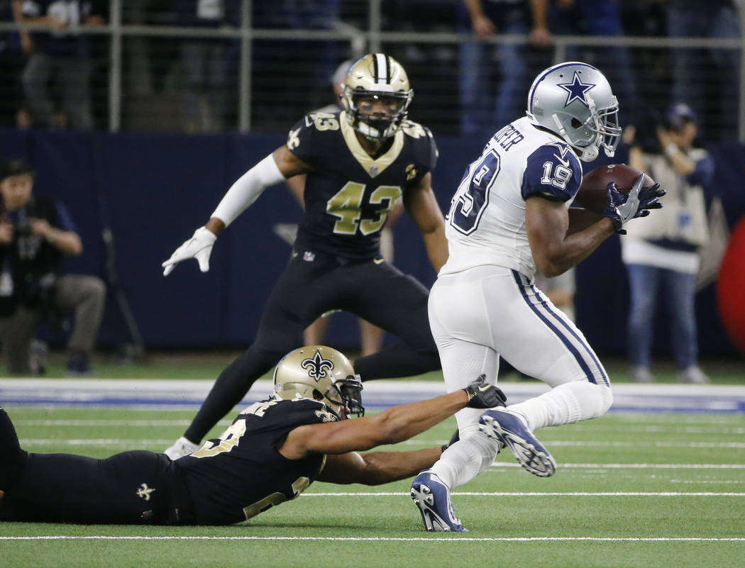 Dallas Cowboys wide receiver Amari Cooper (19) pull in a pass over New Orleans Saints cornerback Marshon Lattimore (23) in the first half of an NFL football game, in Arlington, Texas, Thursday, No ...