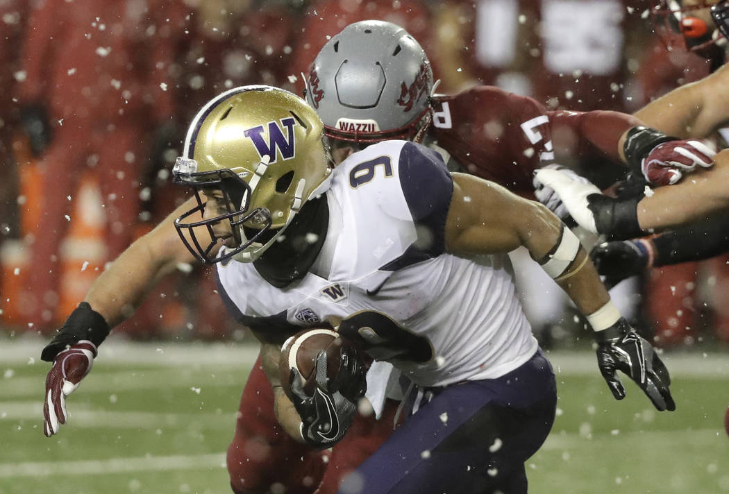 Washington running back Myles Gaskin (9), is tackled by Washington State linebacker Peyton Pelluer as he rushes during the first half of an NCAA college football game, Friday, Nov. 23, 2018, in Pu ...