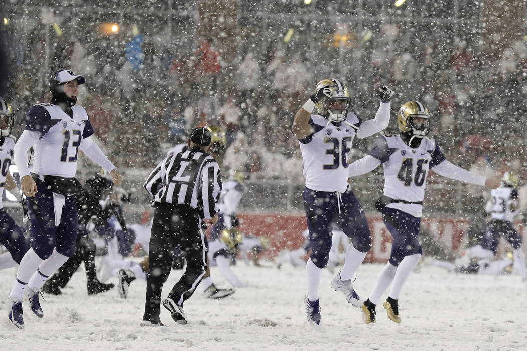 Washington players celebrate as they run onto the field after Washington defeated Washington State 28-15 in an NCAA college football game Friday, Nov. 23, 2018, in Pullman, Wash. (AP Photo/Ted S. ...