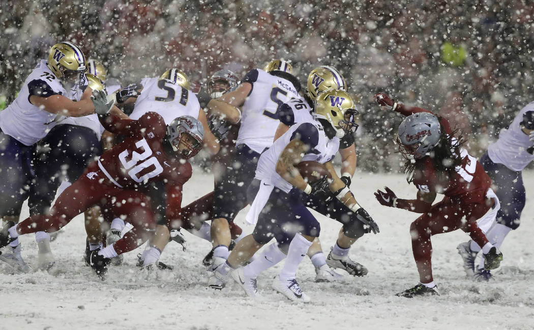 Washington running back Myles Gaskin, center, rushes past Washington State defensive lineman Nnamdi Oguayo (30) and linebacker Jahad Woods, right, during the second half of an NCAA college footbal ...