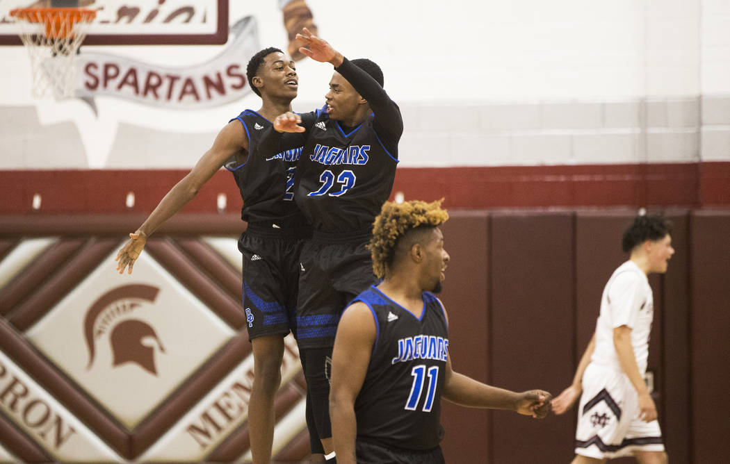 Desert Pines sophomore Dayshawn Wiley (2) celebrates with teammate Darnell Washington (13 after dunking at the end of the second quarter on Wednesday, Nov. 28, 2018, at Cimarron-Memorial High Scho ...