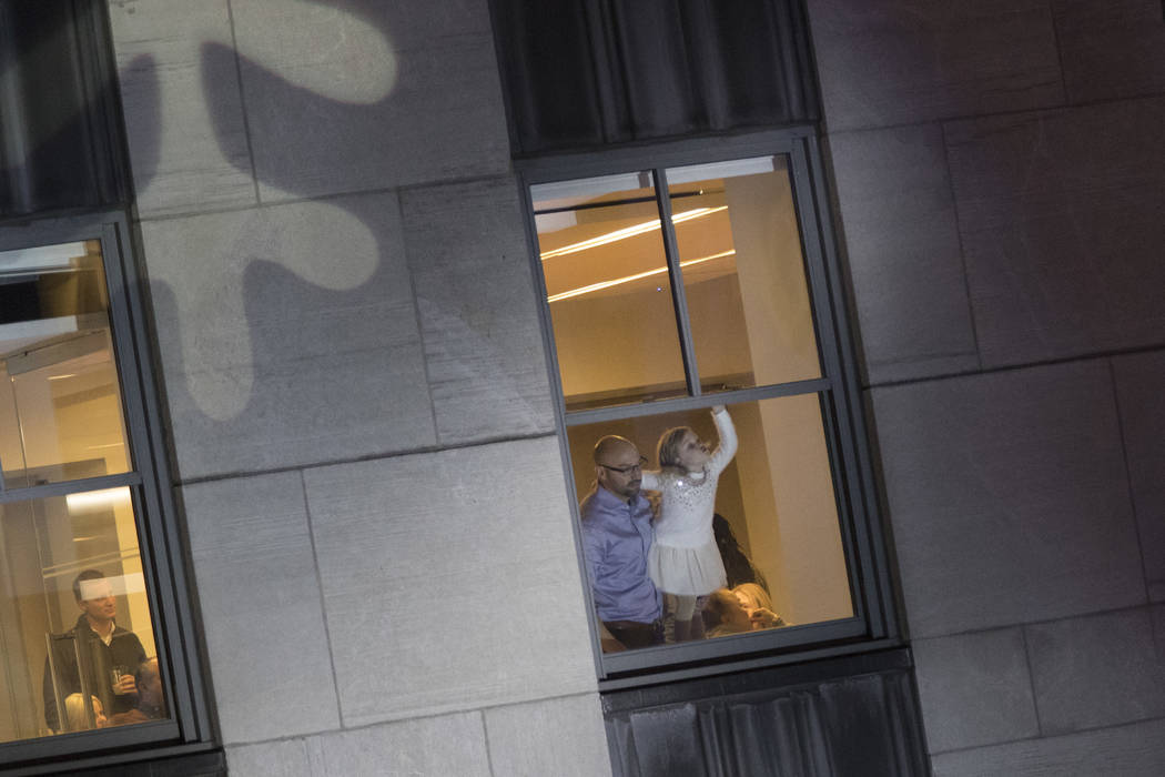 A child waits from an adjoining building for the start of the 86th annual Rockefeller Center Christmas tree lighting ceremony, Wednesday, Nov. 28, 2018, in New York. (AP Photo/Mary Altaffer)