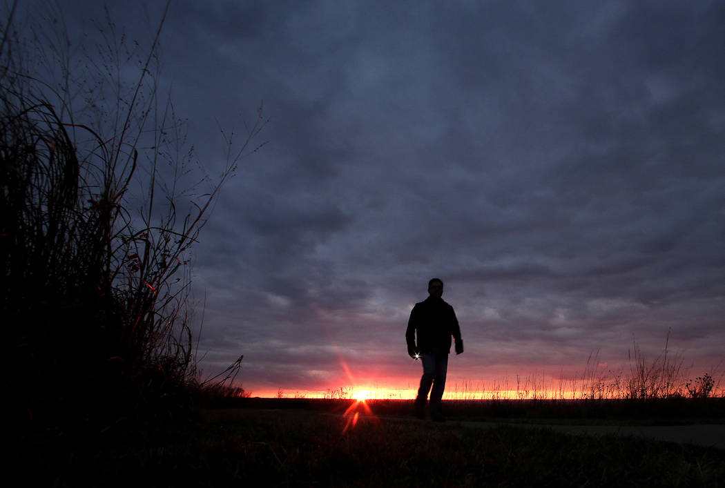 A man walks a trail as he watches the sunset over the Flint Hills at a roadside park near Manhattan, Kan. Suicides and drug overdoses helped lead a surge in U.S. deaths last year, and drove a cont ...