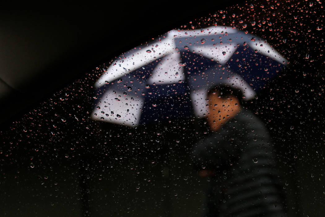 A pedestrian walks with his umbrella in the rain on Fremont Street in Las Vegas, Thursday, Nov. 29, 2018. Chitose Suzuki Las Vegas Review-Journal @chitosephoto