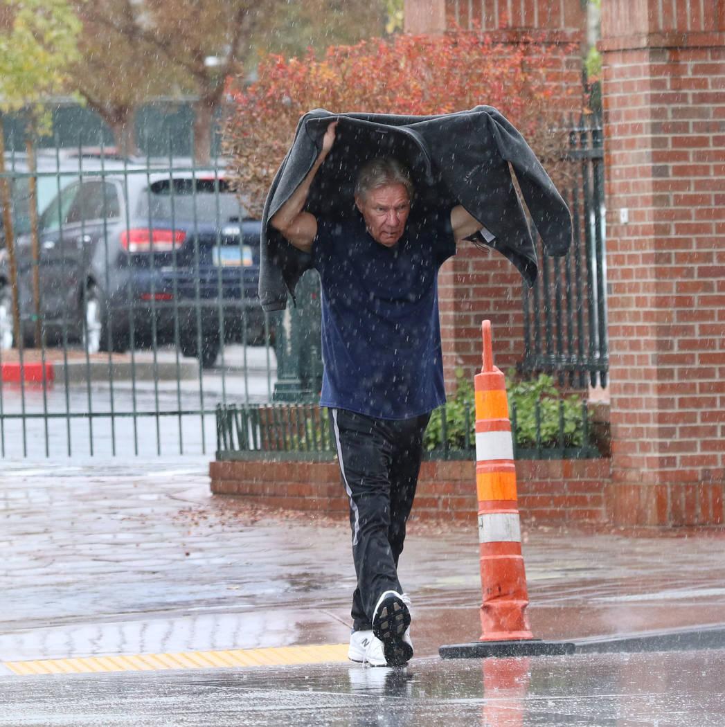 A man crosses Main Street a rainstorm on Thursday, Nov. 29, 2019, in Las Vegas. Bizuayehu Tesfaye Las Vegas Review-Journal @bizutesfaye