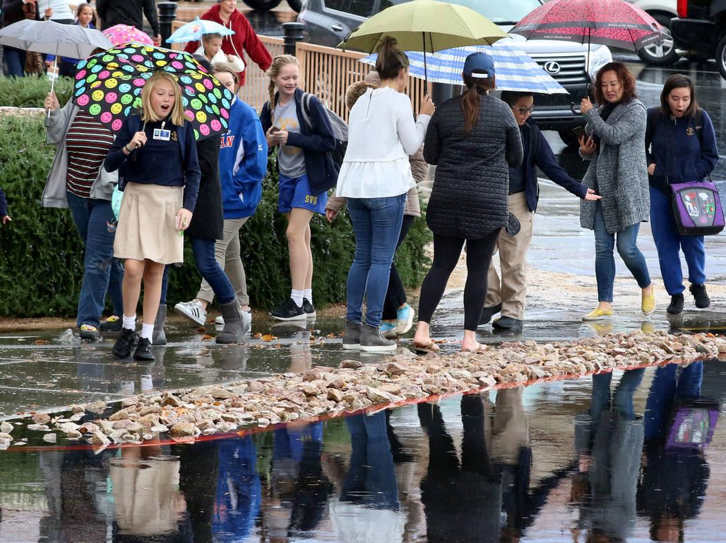Students and parents at St. Viator School avoid a flooded sidewalk as they walk near Eastern Avenue on Thursday, Nov. 29, 2019, in Las Vegas. Bizuayehu Tesfaye Las Vegas Review-Journal @bizutesfaye
