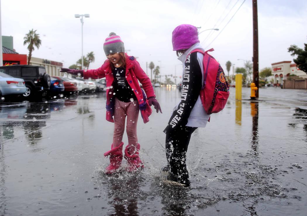 Violette Frankenberg, 6, left, jumps in rain puddles with her sister Scarlette Frankenberg, 8, right, in the parking lot of the Las Vegas Athletic Club in Las Vegas, Thursday, Nov. 29, 2018. Rache ...