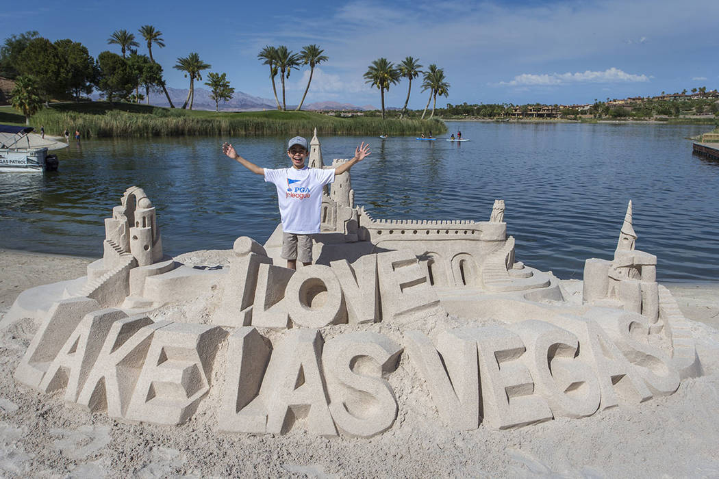 A boy stands by a sand art creation he helped build. (Lake Las Vegas)