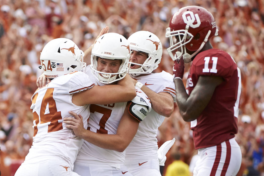 Texas kicker Cameron Dicker (17) celebrates with teammates after kicking the game-winning field goal in the closing seconds of the second half of an NCAA college football game against Oklahoma at ...