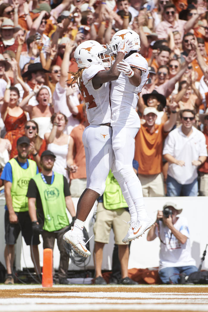Texas wide receiver Lil'Jordan Humphrey, left, celebrates after scoring a touchdown on a 15-yard reception with teammate John Burt (1) against Oklahoma during the second half of an NCAA college fo ...