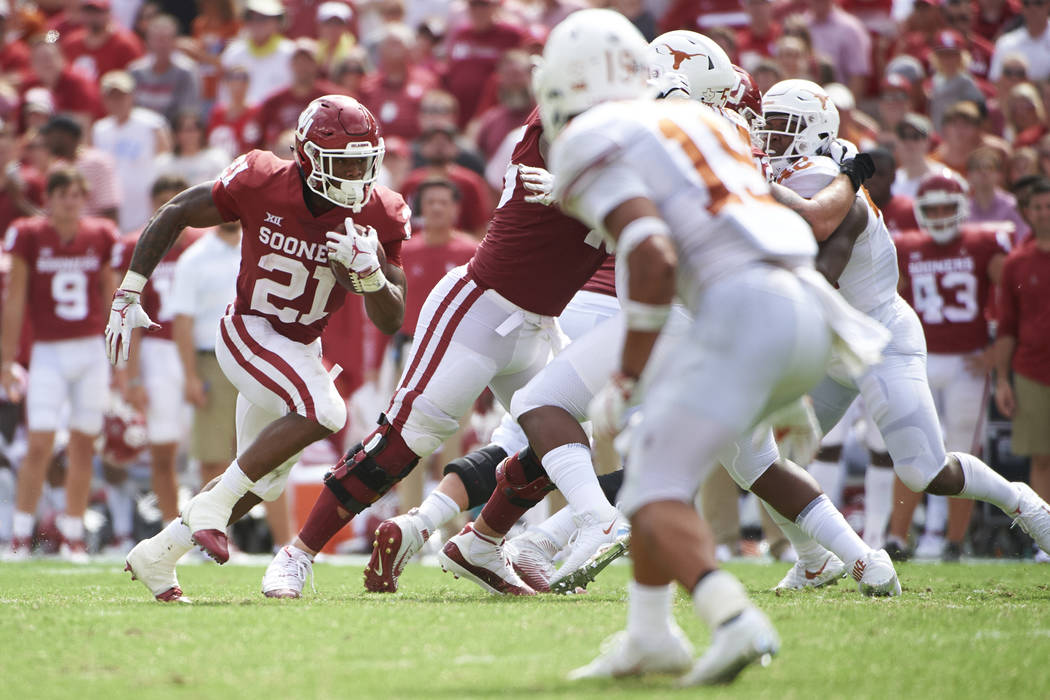 Oklahoma running back Marcelias Sutton (21) breaks free against Texas during the second half of an NCAA college football game at the Cotton Bowl, Saturday, Oct. 6, 2018, in Dallas. (AP Photo/Coope ...