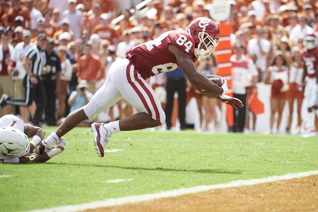 Oklahoma wide receiver Lee Morris (84) dives into the end zone for a touchdown on a 19-yard reception against Texas during the second half of an NCAA college football game at the Cotton Bowl, Satu ...