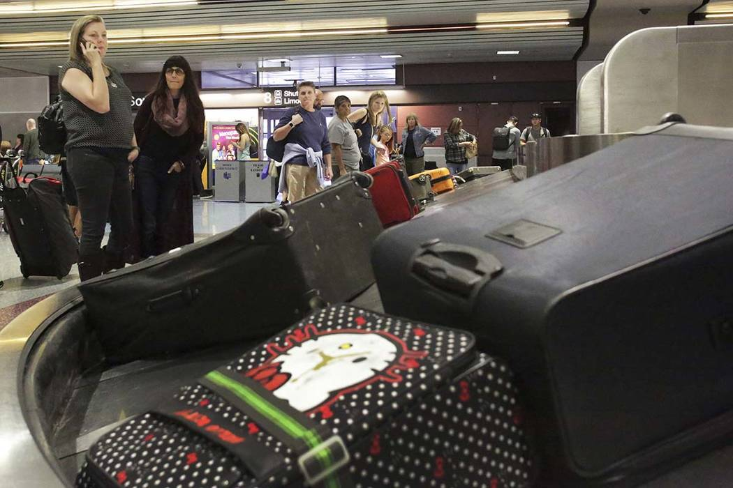 Marriah Pearson, left, of Temecula, California, and Cheryl Bowman of Carlsbad, California, wait for their luggage at baggage claim in McCarran International Airport in Las Vegas, Oct. 19, 2018. (M ...