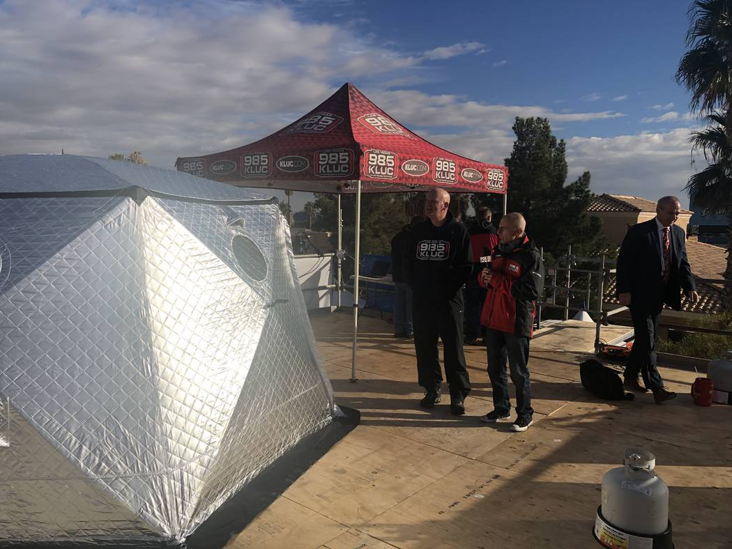 Chet Buchanan is interviewed by Fox 5 reporter Mike Doria next to Buchanan's temporary tent home at the 20th annual KLUC Toy Drive 30 feet above the street at NV Energy's headquarters on West Saha ...