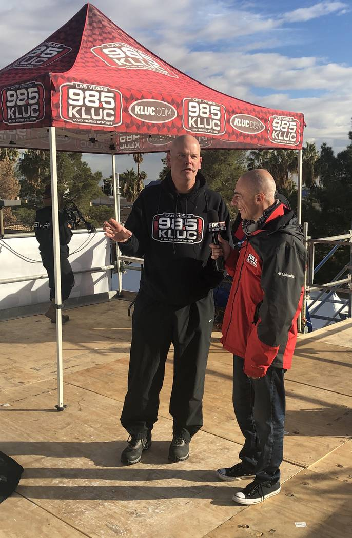 Chet Buchanan is interviewed by Fox 5 reporter Mike Doria at the 20th annual KLUC Toy Drive from his temporary home 30 feet above the street at NV Energy's headquarters on West Sahara Avenue. (Joh ...