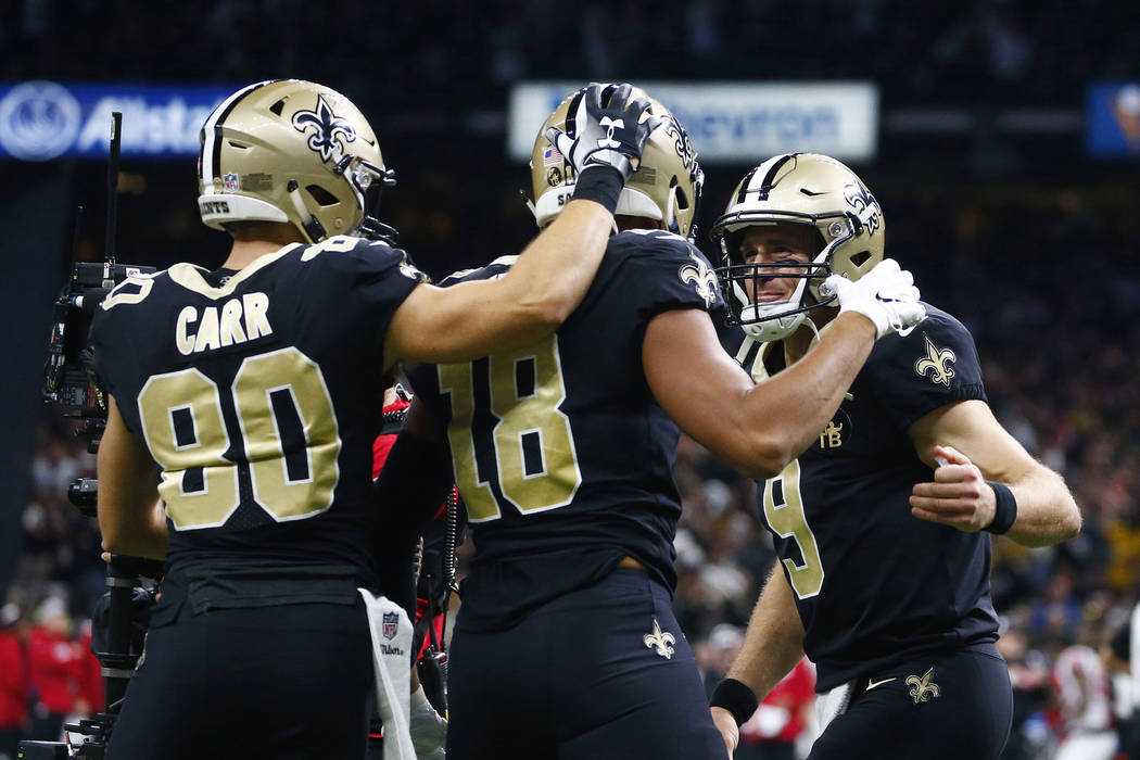 In this Nov. 22, 2018 file photo, New Orleans Saints quarterback Drew Brees (9) and wide receiver Austin Carr (80) celebrate with wide receiver Keith Kirkwood (18) after Brees' touchdown pass to K ...