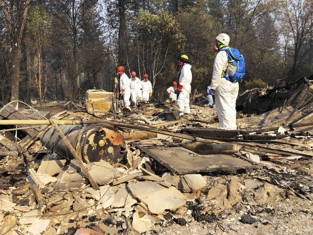 File - In this Nov. 18, 2018 file photo, volunteer members of an El Dorado County search and rescue team search the ruins of a home, looking for human remains, in Paradise, Calif., following a wil ...