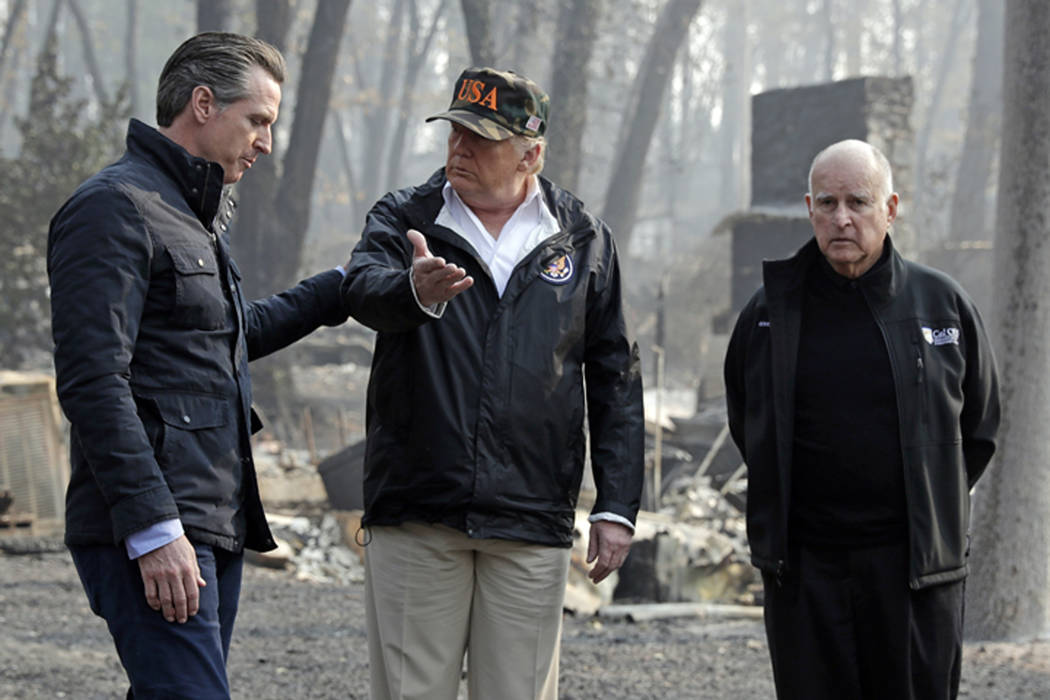 FILE - In this Nov. 17, 2018 file photo, President Donald Trump talks with Gov.-elect Gavin Newsom, left, as California Gov. Jerry Brown listens during a visit to a neighborhood impacted by the Ca ...