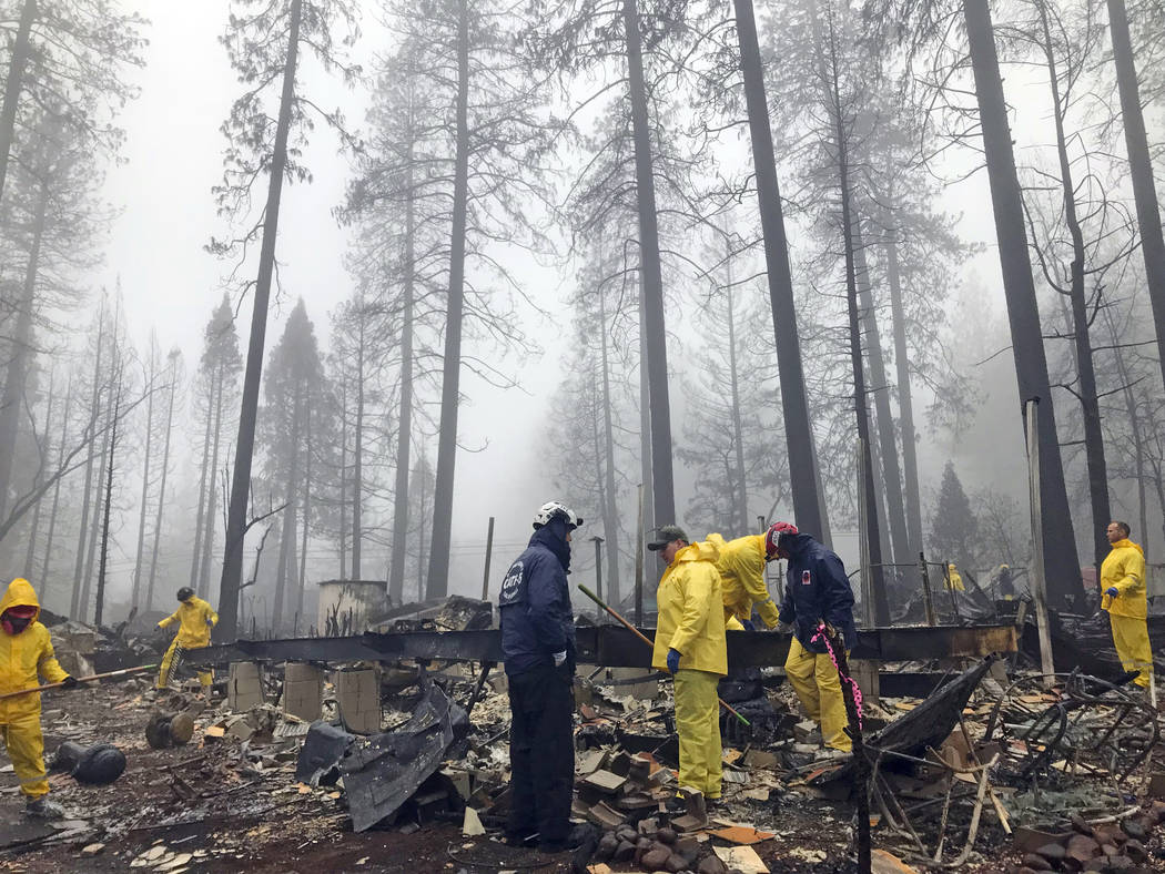 After a brief delay to let a downpour pass, volunteers resume their search for human remains at a mobile home park in Paradise, Calif., Friday, Nov. 23, 2018. A team from Orange County in Southern ...