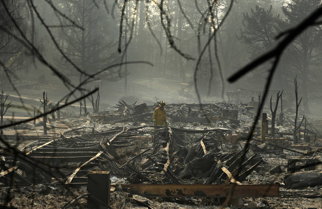 FILE - In this Nov. 16, 2018, file photo, a firefighter searches for human remains in a trailer park destroyed in the Camp Fire, in Paradise, Calif. The massive wildfire that killed dozens of peop ...