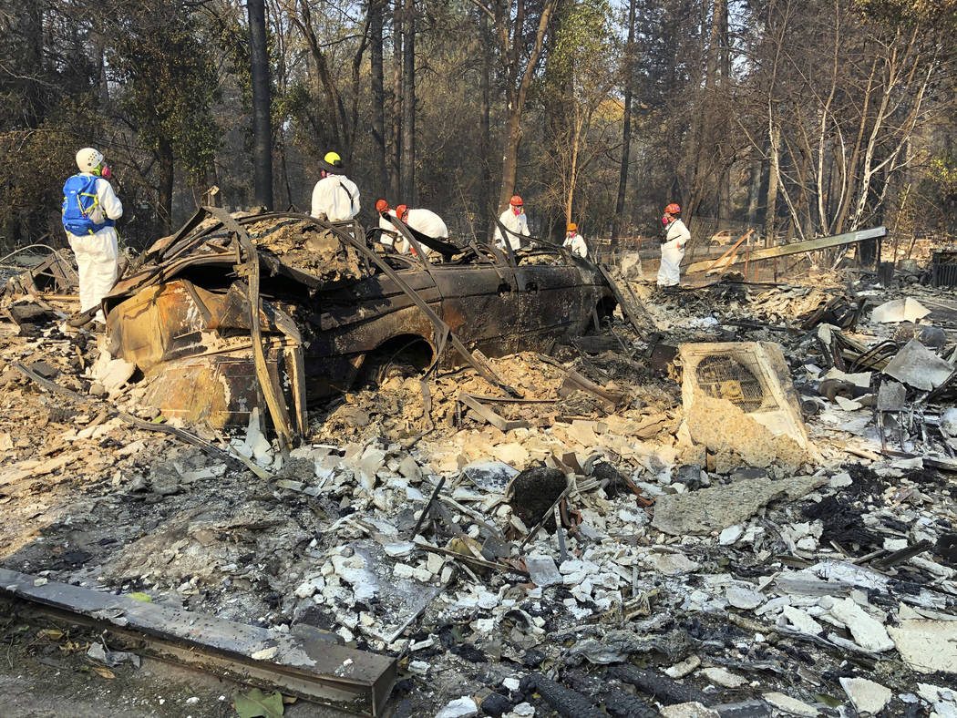 Volunteer members of an El Dorado County search and rescue team search the ruins of a home and vehicle, looking for human remains, in Paradise, Calif., Sunday, Nov. 18, 2018, following a Northern ...