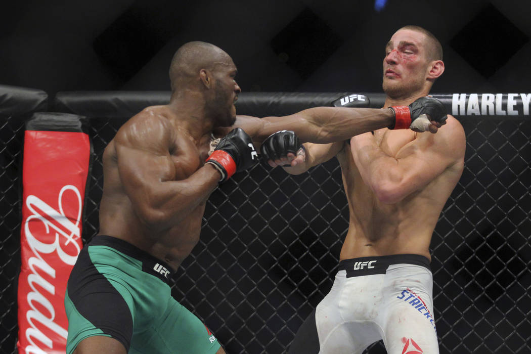 Welterweight Kamaru Usman, left, lands a punch on Sean Strickland during a mixed martial arts bout at UFC 210, Saturday, April 8, 2017, in Buffalo, N.Y. (AP Photo/Jeffrey T. Barnes)