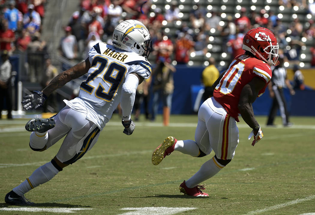 Kansas City Chiefs wide receiver Tyreek Hill, right, runs back a punt return defended by Los Angeles Chargers cornerback Craig Mager during the first half of an NFL football game in Carson, Calif. ...