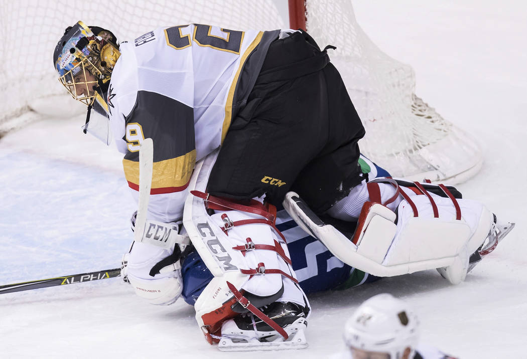 Vancouver Canucks' Tim Schaller, bottom, slides under Vegas Golden Knights goalie Marc-Andre Fleury during the second period of an NHL hockey game Thursday, Nov. 29, 2018, in Vancouver, British Co ...